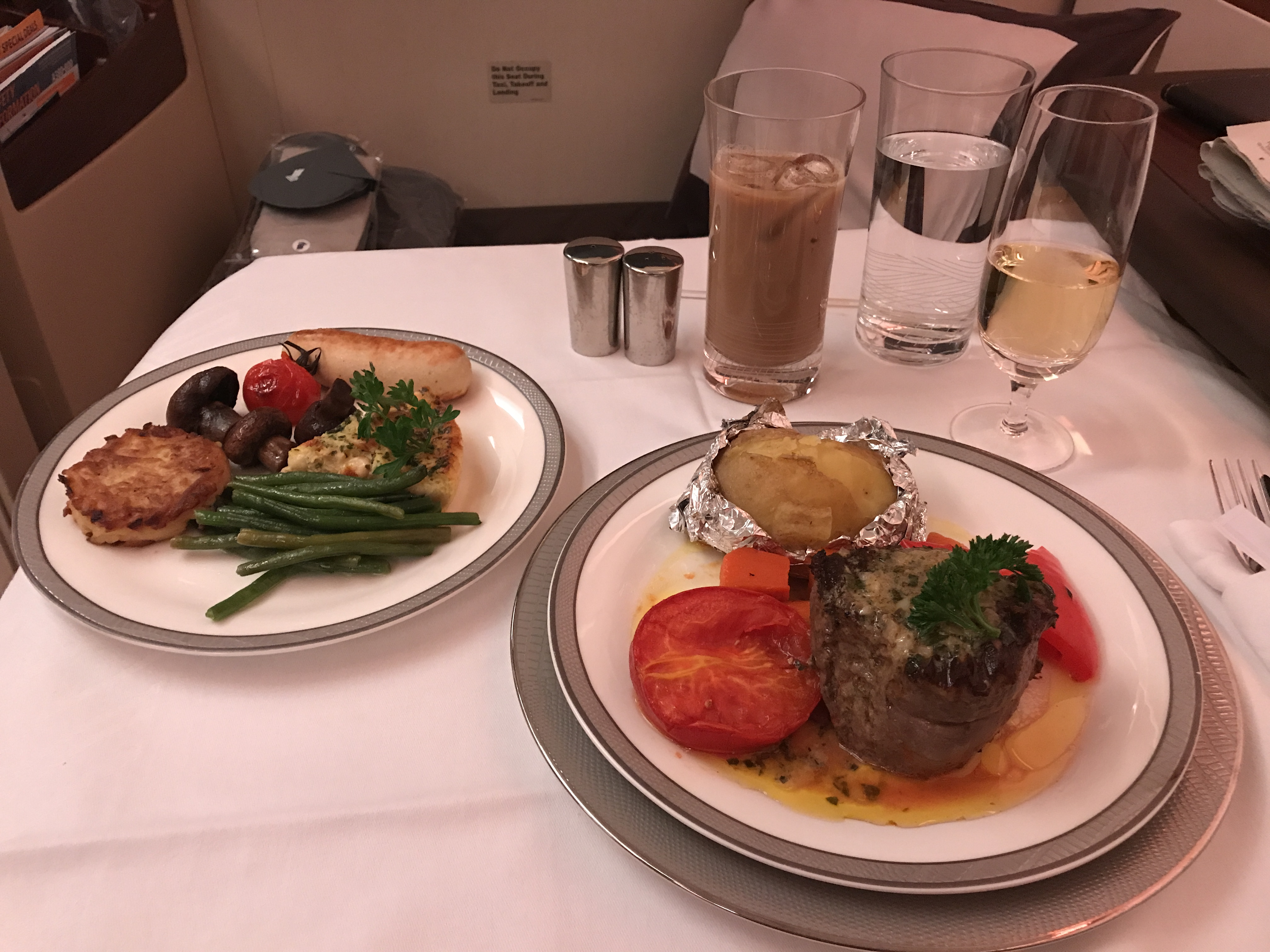At left: goat cheese quiche with green beans, rosti potatoes, mushrooms, and veal sausage. At right: Steak with a baked potato.